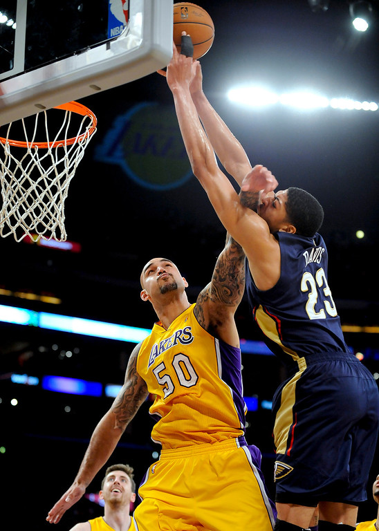 . Los Angeles Lakers center Robert Sacre (50) fouls New Orleans Pelicans forward Anthony Davis (23) during the first half of an NBA basketball game, Tuesday, March 4, 2014, in Los Angeles.(AP Photo/Gus Ruelas)