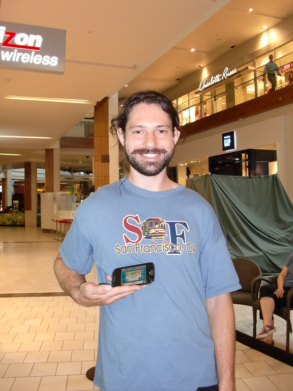 . Drew Blumfield of West Hills, holding his Samsung Galaxy S3 phone, waits outside the Verizon Wireless store at the Westfield Topanga mall in Canoga Park to buy a top-of-the-line iPhone 4s on the handset\'s debut day, Sept. 20, 2013. He planned to sell the new iPhone on eBay and make a $400 to $600 profit. (Photo by Steven Rosenberg/Los Angeles Daily News)
