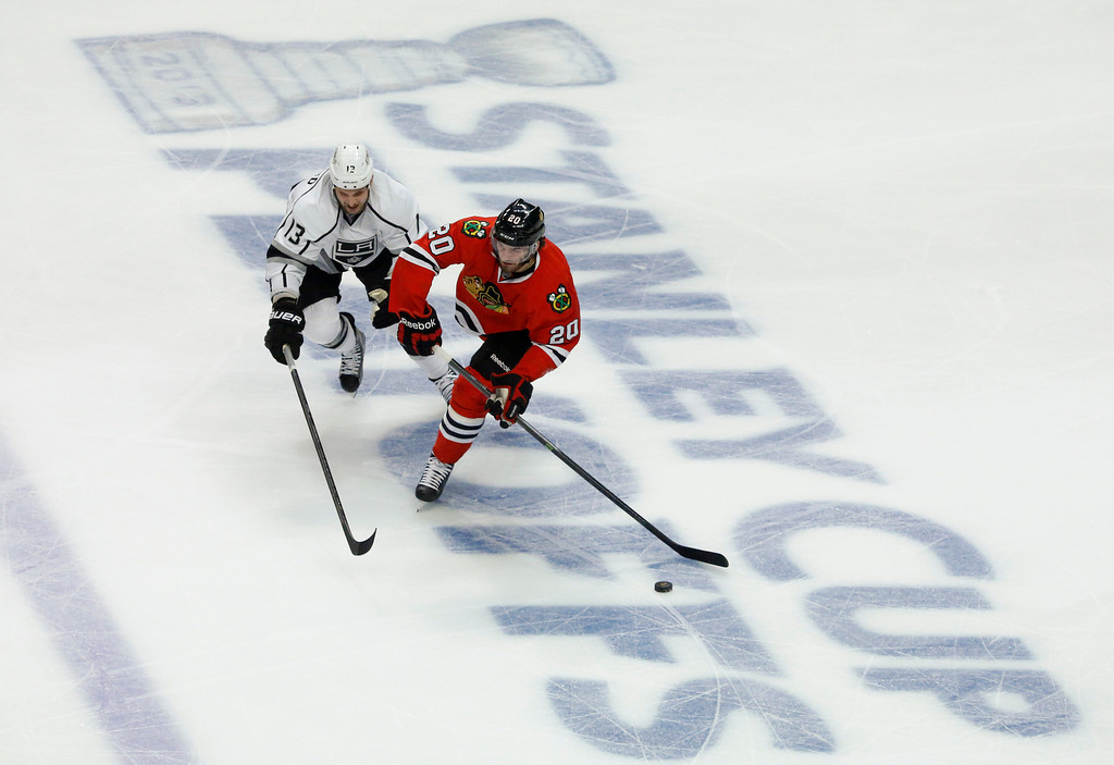 . Chicago Blackhawks left wing Brandon Saad (20) brings the puck up the ice against Los Angeles Kings left wing Kyle Clifford (13) during the first period in Game 1 of the NHL hockey Stanley Cup Western Conference finals Saturday, June 1, 2013, in Chicago. (AP Photo/Charles Rex Arbogast)