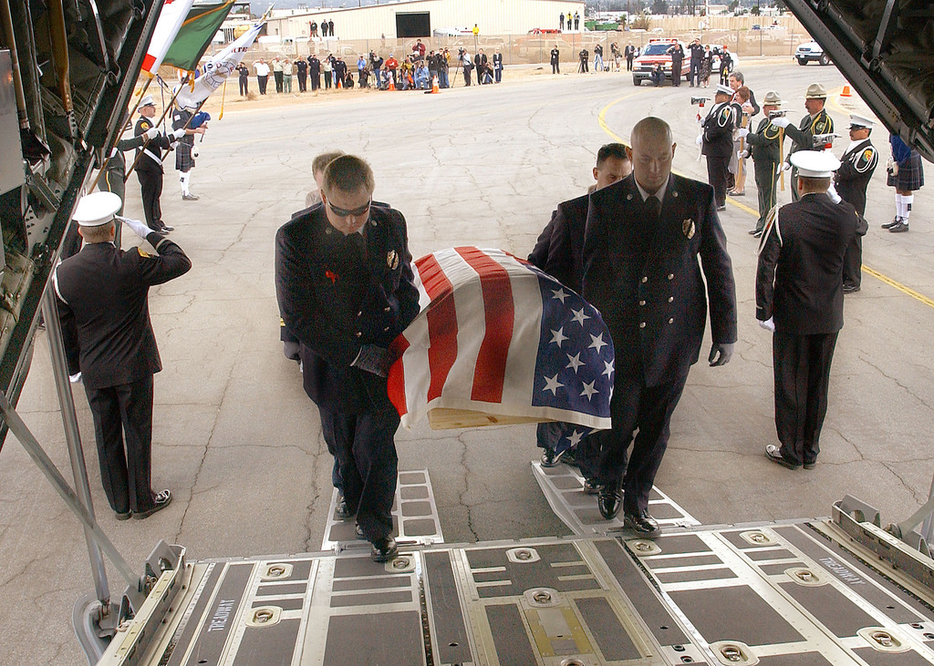 . EL CAJON, CA - NOVEMBER 3:  Novato firefighters Shawn Kreps (L) and Barrett Smith lead pallbearers carry the casket of firefighter Steven Rucker into the cargo area of a California Air National Guard C-130 at Gillespie Field Airport November 3, 2003 in El Cajon, California. Doug McDonald survived the Cedar Fire, one of California\'s largest wild fires, which claimed Rucker\'s life October 29, 2003.  (Photo by Alex J. Koenig/U.S. Air Force via Getty Images)