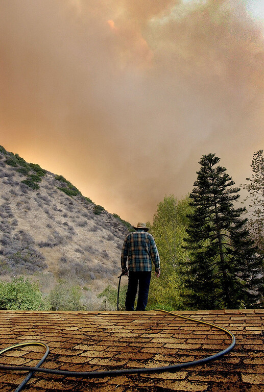 . After wetting down the roof of his home of 20 years under smoke-filled skies, Bob McCary stares at billows of smoke from fire  in Hopper Canyon in Fillmore, California, Sunday afternoon, Oct. 26, 2003.  The fire known as the Piru fire, that had been approcaching containment, flared up on Sunday.  (AP Photo/Reed Saxon)