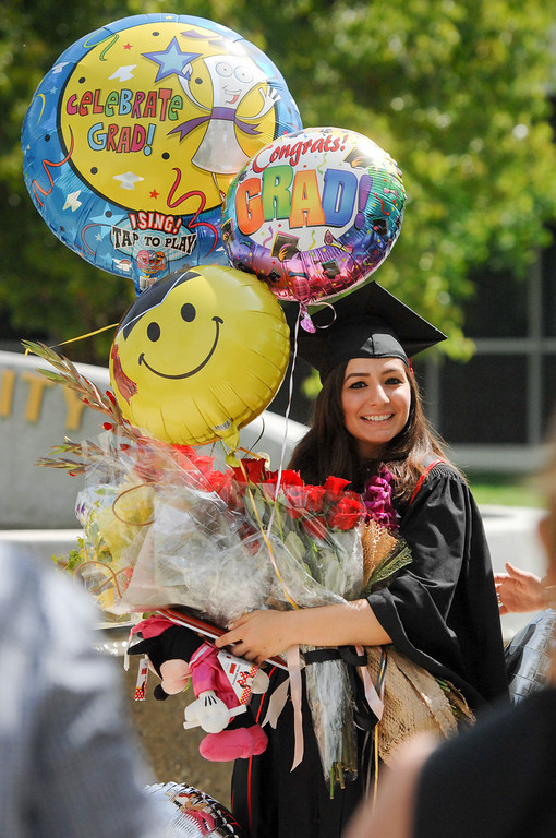 . Communication studies major Silva Atsilatsyan has her picture taken with graduation gifts following the CSUN the commencement ceremony, Tuesday, May 21, 2013. (Michael Owen Baker/L.A. Daily News)