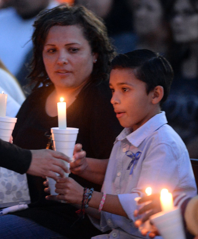 . Veronica Soriano, mother of Adrian Castro, 19, and her son, Solan, 10, hold candles during a memorial gathering for him at El Monte High School Monday evening April 14, 2014. Castro was one of nine students killed in the bus crash in Orland, Calif. (Staff Photo by Keith Durflinger/San Gabriel Valley Tribune)