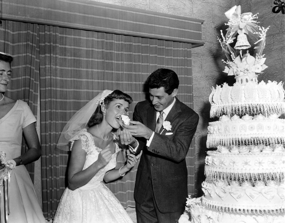. Singer Eddie Fisher, 26, feeds a piece of wedding cake to his bride, actress Debbie Reynolds, 23, following their marriage at Grossinger, N.Y., on Sept. 26, 1955.  (AP Photo/Marty Lederhandler)