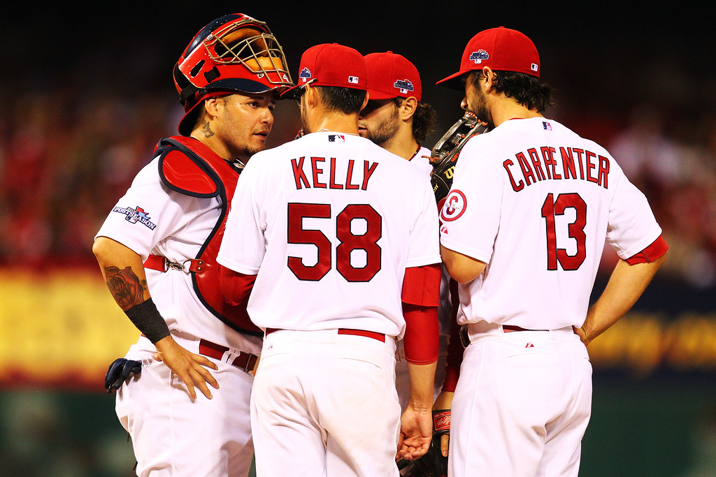 . ST LOUIS, MO - OCTOBER 11:  Joe Kelly #58 talks to Yadier Molina #4 and Matt Carpenter #13 of the St. Louis Cardinals on the mound during Game One of the National League Championship Series against the Los Angeles Dodgers at Busch Stadium on October 11, 2013 in St Louis, Missouri.  (Photo by Dilip Vishwanat/Getty Images)