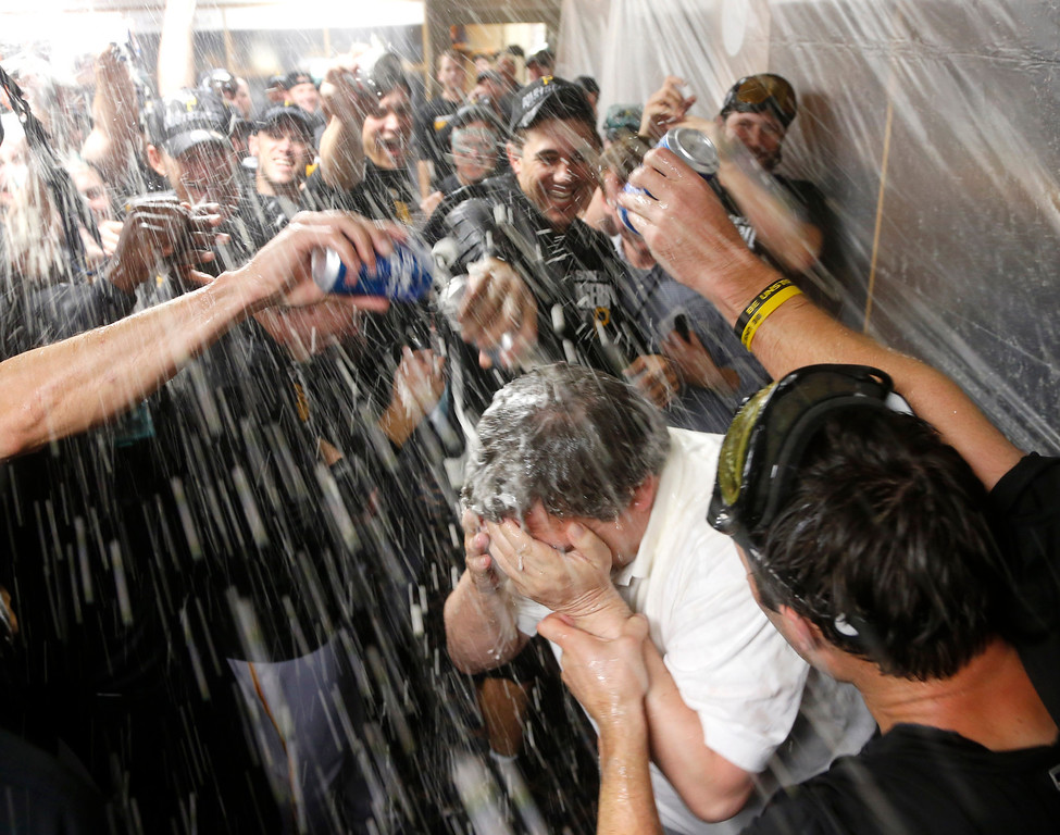 . The Pittsburgh Pirates douse traveling secretary Greg Johnson with champagne and beer after a baseball game and 2-1 win over the Chicago Cubs Monday, Sept. 23, 2013, in Chicago. Johnson has been in his post for 30 years. (AP Photo/Charles Rex Arbogast)