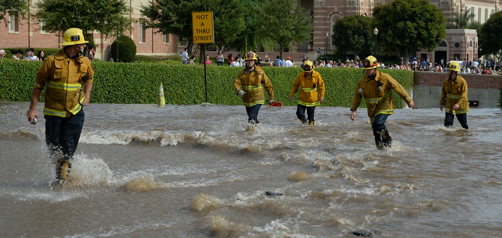 . July 29,2014. Westwood CA,  L.A. city firefighters look for anyone trapped in the underground parking lot after a major water main break sent a geyser of water blasting through Sunset Boulevard north of the UCLA campus Tuesday, sending mud and water cascading down the street and inundating a number of vehicles as it made its way onto the campus. Photo by Gene Blevins/LA DailyNews