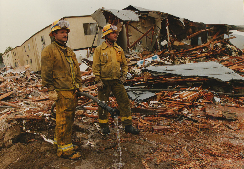 . Firefighters look over the rubble that was at one time the Northridge Meadows three-story apartment complex. The apartments were home to more than 400 people, sixteen were killed as the first floor collapsed in the violent shaking. The death toll at the complex was more than 25 percent of the total fatalities of the entire quake. Northridge, CA. 1/17/1994, photo by (John McCoy/Los Angeles Daily News)