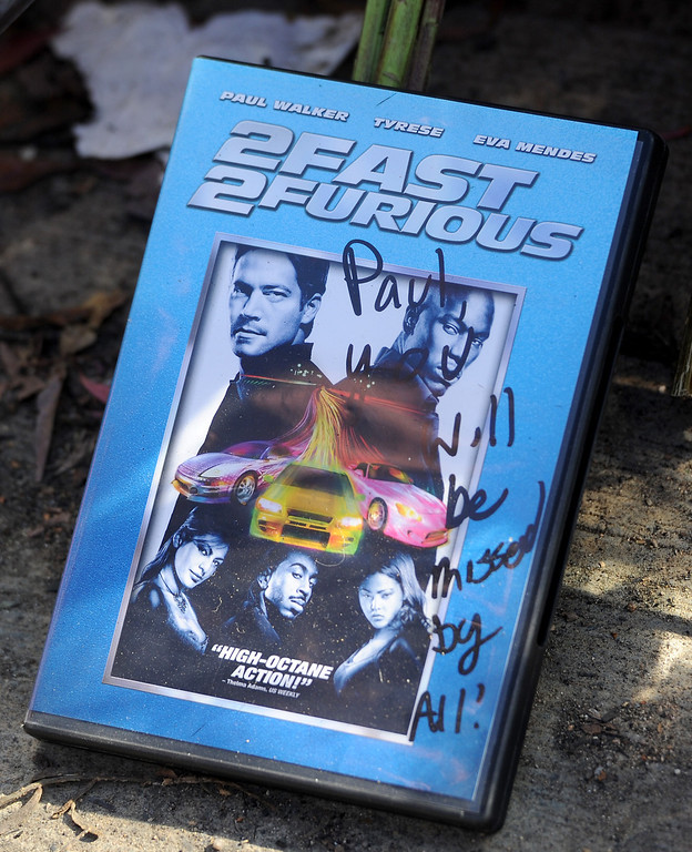 ". A ""2 Fast 2 Furious\"" DVD at the memorial for Paul Walker and Roger Rodas, Sunday, December 1, 2013, at the scene of their fatal crash site in Valencia. (Photo by Michael Owen Baker/L.A. Daily News)"