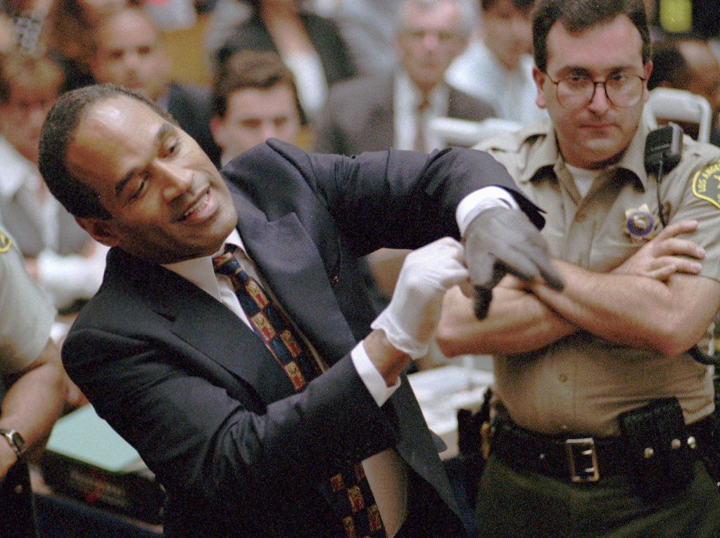 . Murder defendant O.J. Simpson grimaces as he tries on one of the leather gloves prosecutors say he wore the night his ex-wife Nicole Brown Simpson and Ron Goldman were murdered, during the Simpson double-murder trial Thursday, June 15, 1995, in Los Angeles.  O.J. Simpson\'s prosecutors rested Thursday, July 6, 1995 after five  months and 58 witnesses in a legal drama that transfixed the nation with a  tale of a football hero turned murderer.(AP Photo/Sam Mircovich, Pool)