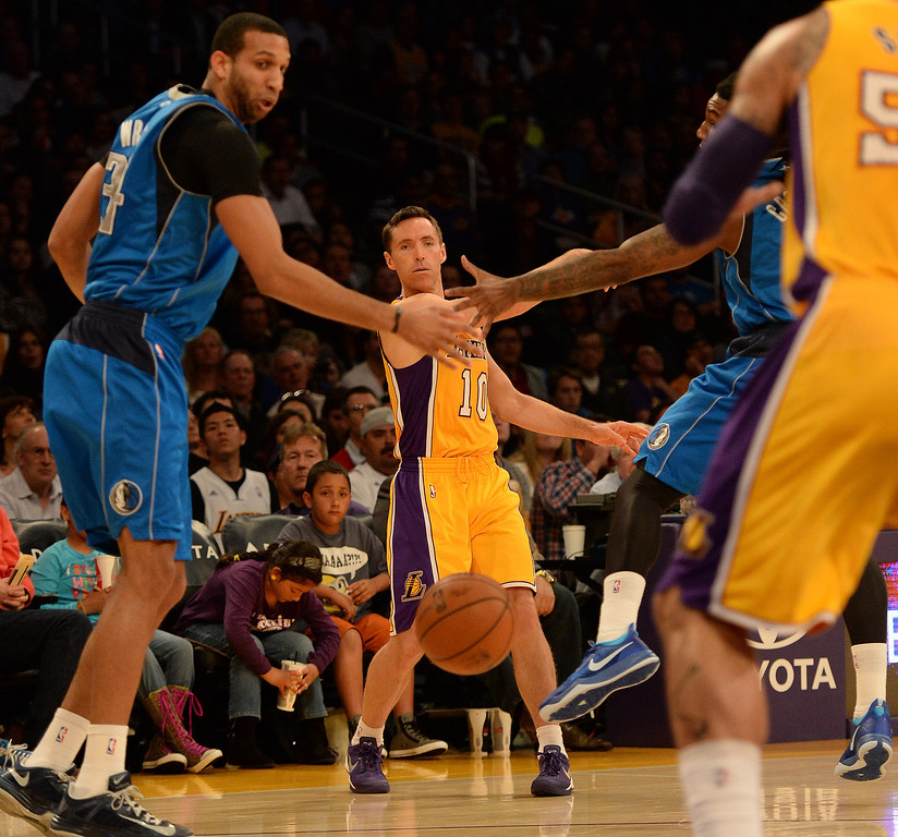 . Los Angeles Lakers guard Steve Nash (10) passes in between the defense of Dallas Mavericks forward Brandan Wright (34) and forward Jae Crowder, right, in the first quarter during an NBA basketball game in Los Angeles, Calif., on Friday, April 4, 2014.  (Keith Birmingham Pasadena Star-News)