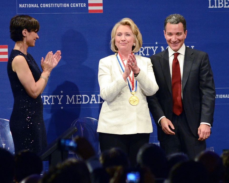 . PHILADELPHIA, PA -  SEPTEMBER 10:  Former Secretary of State Hillary Rodham Clinton (C) receives the 2013 Liberty Medal from Jeffrey Rosen, president and CEO of the National Constitution Center as host Elizabeth Vargas applauds September 10, 2013 in Philadelphia, Pennsylvania. Given annually, the medal aims to recognize leadership in the pursuit of freedom.  (Photo by William Thomas Cain/Getty Images)