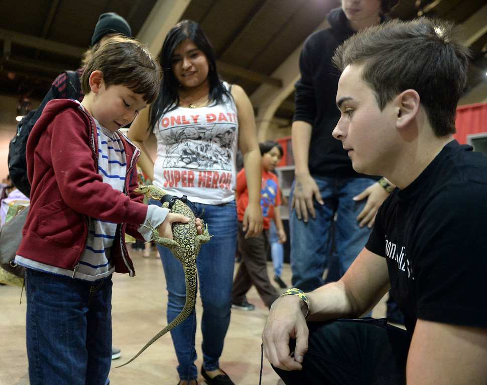 ". David Silva, right, of the Southern California Herpetology Association & Rescue lets six year-old Zac Wu of La Canada hold ""Dexter\"" the Quince monitor lizard as Elizabeth Corona of Camarillo looks on during the Reptile Super Show which is the world\'s largest reptile show with more than 500 tables of rare & unique animals including lizards, turtles, frogs, supplies at the Fairplex in Pomona, Calif., on Saturday, Jan.4, 2014.   (Keith Birmingham Pasadena Star-News)"