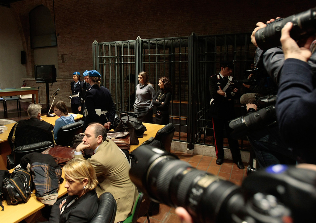 . Members of the media take photographs of US murder suspect Amanda Knox, second from left in the background, during a hearing in her appeals trial in the murder of her British roommate Meredith Kercher, in Perugia\'s courthouse, Italy, Wednesday, Nov. 24,  2010.  (AP Photo/Gregorio Borgia)