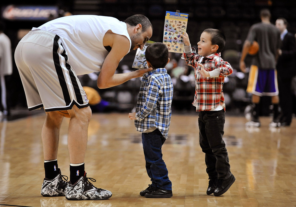 . San Antonio Spurs guard Manu Ginobili of Argentina visits with his twin sons, Dante and Nicola, before an NBA basketball game against the Los Angeles Lakers on Friday, March 14, 2014. (AP Photo/Bahram Mark Sobhani)