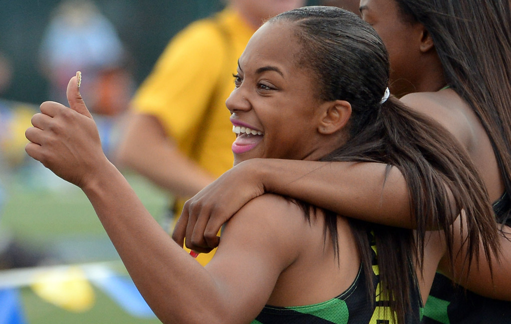 . Long Beach Poly\'s Jade Lewis, left, gives the thumbs-up as she hugs teammate Arianna Washington after Washington won the division 1 100 meter dash during the CIF Southern Section track and final Championships at Cerritos College in Norwalk, Calif., Saturday, May 24, 2014. 