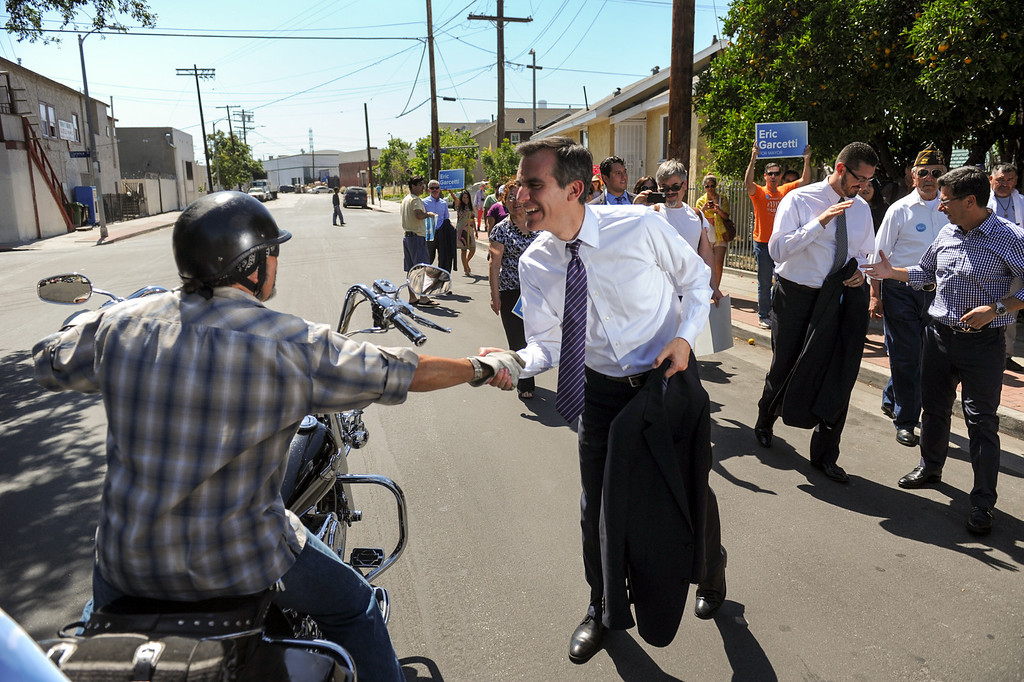 . A motorcycle rider greets mayoral candidate Eric Garcetti during his walk around East Los Angeles, Monday, May 20, 2013. Garcetti made a Whistle Stop Tour of L.A. using the Expo, Gold and Red metro lines to greet voters in Los Angeles. (Michael Owen Baker/Staff Photographer)