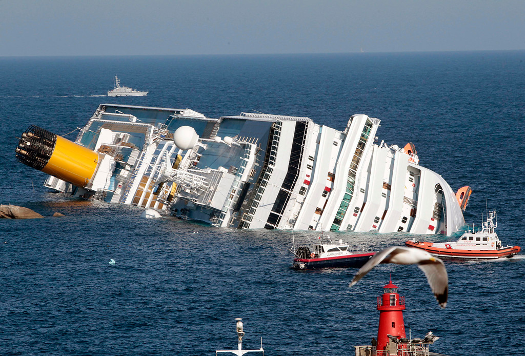 . The luxury cruise ship Costa Concordia lays on its side after running aground the tiny Tuscan island of Giglio, Italy, Saturday, Jan. 14, 2012.  (AP Photo/Gregorio Borgia)