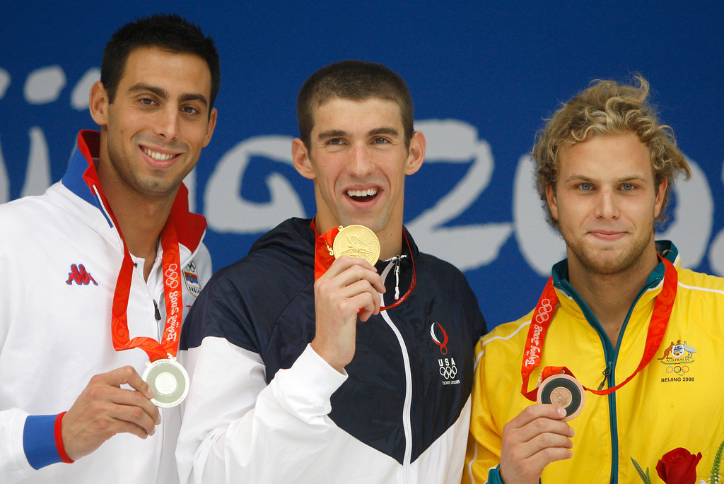 . Gold medalist United States\' Michael Phelps, center, reacts during the presentation ceremony for the men\'s 100-meter butterfly final during the swimming competitions in the National Aquatics Center at the Beijing 2008 Olympics in Beijing, Saturday, Aug. 16, 2008. At left is Serbia\'s Milorad Cavic, who took silver and and at right is bronze medalist Andrew Lauterstein from Australia.  (AP Photo/Mark Baker)