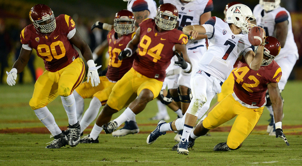 . USC defenders pressure Arizona quarterback B.J. Denker #7 during their game at the Los Angeles Memorial Coliseum Thursday, October 10, 2013. (Photo by Hans Gutknecht/Los Angeles Daily News)
