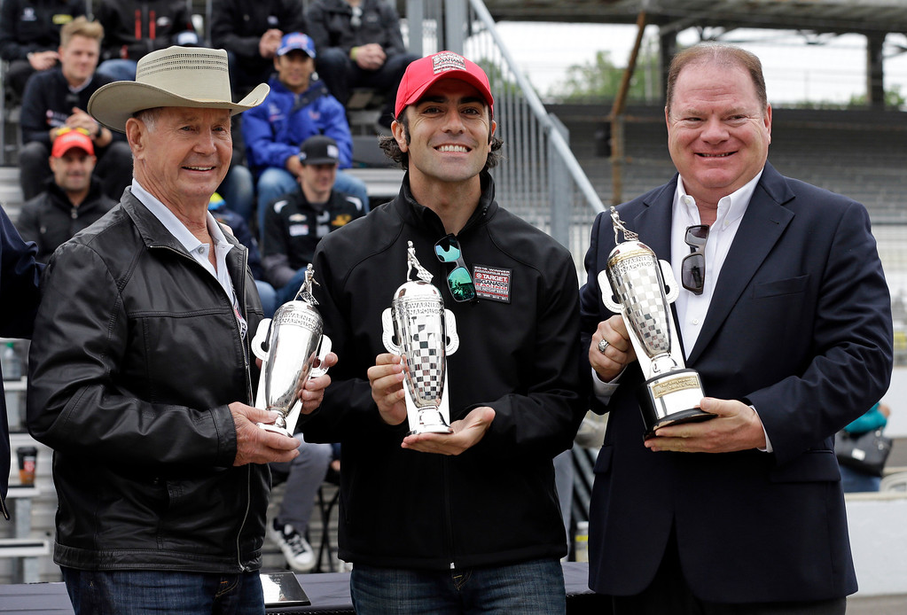 ". In this May 25, 2013 file photo, the 2012 Indy 500 champion Dario Franchitti, of Scotland, center, along with car owner Chip Ganassi, right, and 1963 champion Parnelli Jones receive ""Baby\"" Borg-Warner trophies during the public drivers meeting for the Indianapolis 500 auto race in Indianapolis. (AP Photo/Darron Cummings, File)"