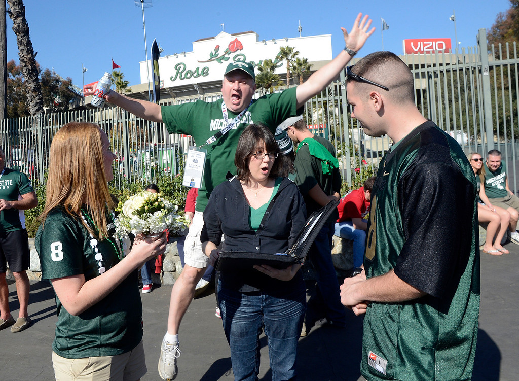 . A fan jumps behind as Julie Dove, center, marries Tom Mapley, right, a Michigan State University police officer and Elena Upperstrom prior to the 100th Rose bowl game in Pasadena, Calif., on Wednesday, Jan.1, 2014. 