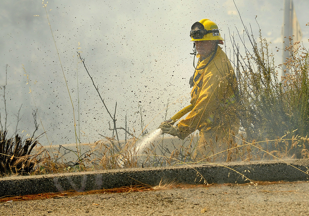 . A firefighter puts water on a hot spot near the 2 freeway and the Harvey Dr. southbound off-ramp. A brush fire burned nearly 75 acres in an area north and east of the 134 and 2 freeways in Glendale. Residents on Chevy Chase, east of the 2 freeway were evacuated as helicopters, hand crews and firefighters battled the fire that burned through the mountains and canyons. Glendale, CA 5/3/2013(John McCoy/Staff Photographer)