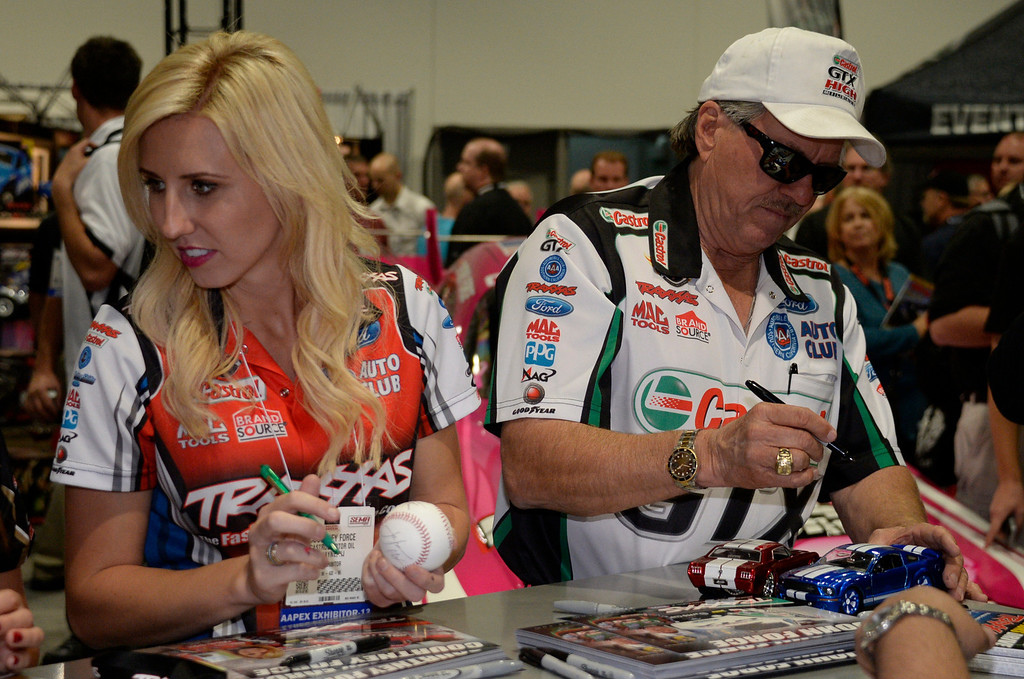 . Nov 5,2013 Las Vegas NV. USA. NHRA Funny Car Champion John Force and his daughter  Courtney sign autographs at the traxxas booth during the first day of the 2013 SEMA auto show.