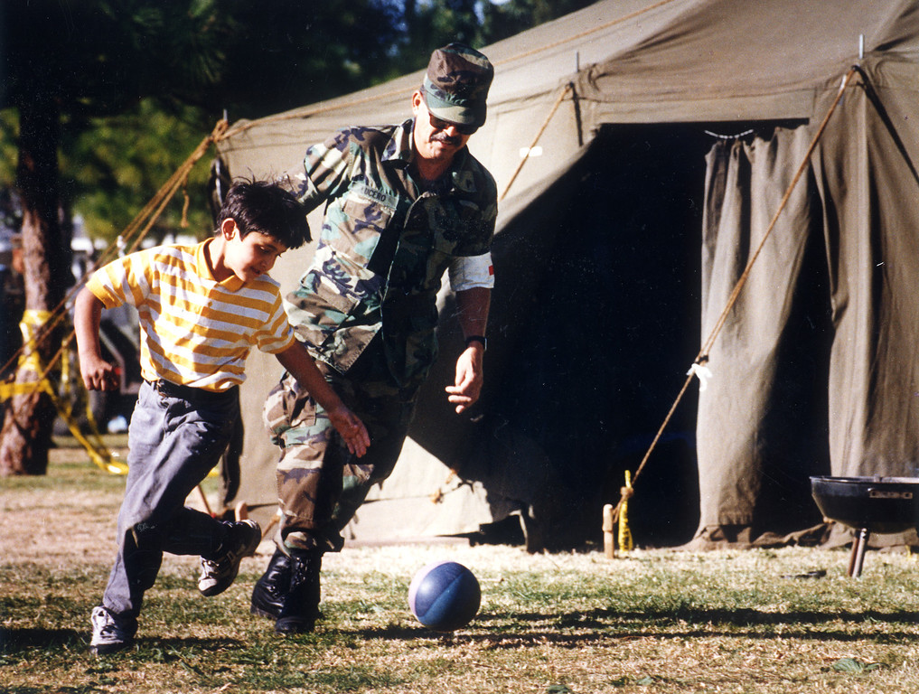 . National Guardsman Abraham Lucero plays soccer with a child at a tent city in Reseda Park.   1/23/94.   (Los Angeles Daily News file photo)