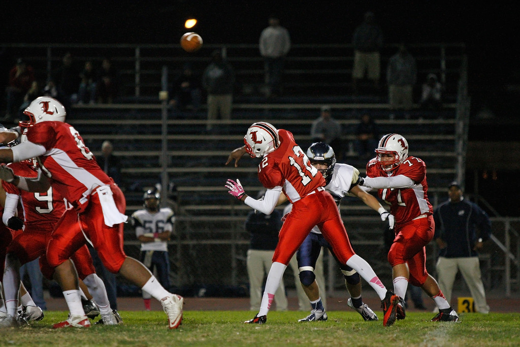 . Quarterback Chris Murray #12 of Lawndale drops back to pass against the defense of El Segundo in a Pioneer League matchup at Leuzinger High School on Friday, October 11, 2013 in Lawndale, Calif.  (Michael Yanow / For the Daily Breeze)
