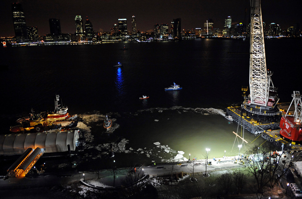 """. The wreckage of US Airways Flight 1549 remains submerged in the icy waters off lower Manhattan Saturday, Jan. 17, 2009 as workers continue to try to lift the Airbus A320 out of the water. Investigators began interviewing the pilot, Chesley B. \""""Sully\"""" Sullenberger, and his co-pilot for the first time Saturday. Sullenberger guided the crippled aircraft into the river on Thursday afternoon, saving the lives of all 155 people on board.  (AP Photo/ Louis Lanzano)"""