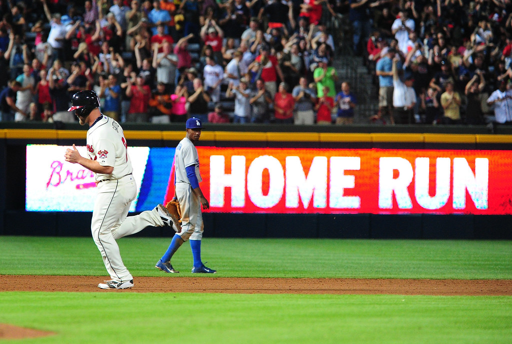 . Evan Gattis #24 of the Atlanta Braves rounds the bases after hitting an eighth inning pinch hit home run against the Los Angeles Dodgers at Turner Field on May 18, 2013 in Atlanta, Georgia. Braves won 3-1   (Photo by Scott Cunningham/Getty Images)