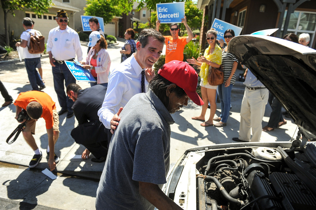 . Mayoral candidate Eric Garcetti talks with a man fixing his car in East Los Angeles during his Whistle Stop Tour of LA, Monday, May 20, 2013. Garcetti used the Expo, Gold and Red metro lines to greet voters in Los Angeles. (Michael Owen Baker/Staff Photographer)