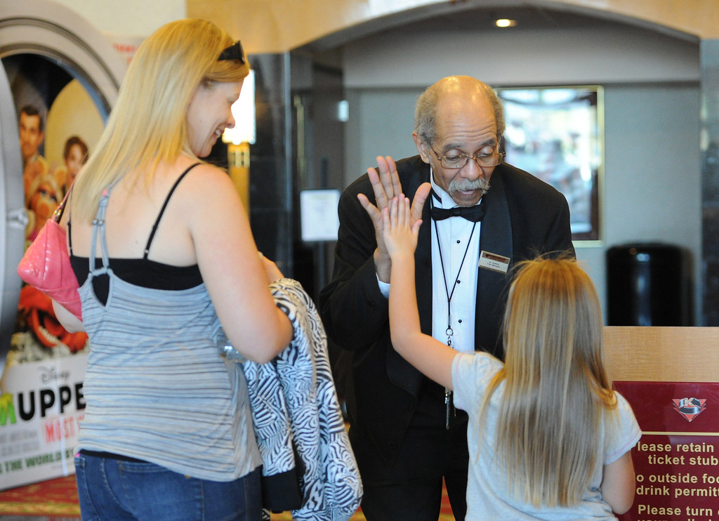 . Al Harris, floor manager of the Krikorian Premier Theatre, greets Amy Royalty and daughter Haliee, 7, before the start of their movie, Thursday, in Redlands Feb. 13, 2014. Harris has become a local icon collecting tickets and giving high fives to moviegoers since being hired by Krikorian in 1992.  (John Valenzuela/Photographer)