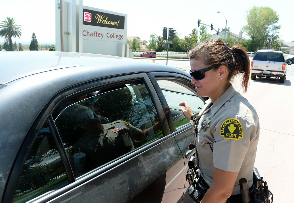 . Sheriff deputy Anna Mata searches a vehicle leaving the Chaffey College campus Thursday. The Chaffey College campus in Rancho Cucamonga was lockdown by campus police at approximately 1:15 p.m Thursday August 21, 2014 after a report was made about a maie with anti-goverment patches on his vest, wearing black combat boots, black pants and a black backpack. The threat was never confirmed and no one was taken into custody. The campus was under lockdown for over an hour before it was lifted. Classes have been cancelled for the rest of the day.  (Will Lester/Inland Valley Daily Bulletin)