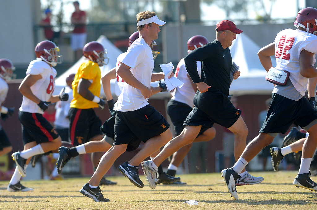 . USC head coach Lane Kiffin runs with his team during a practice at the Howard Jones Field at USC Monday August 19, 2013.  The Trojans start the season on August 29th with a game against Hawaii.(Andy Holzman/Los Angeles Daily News)