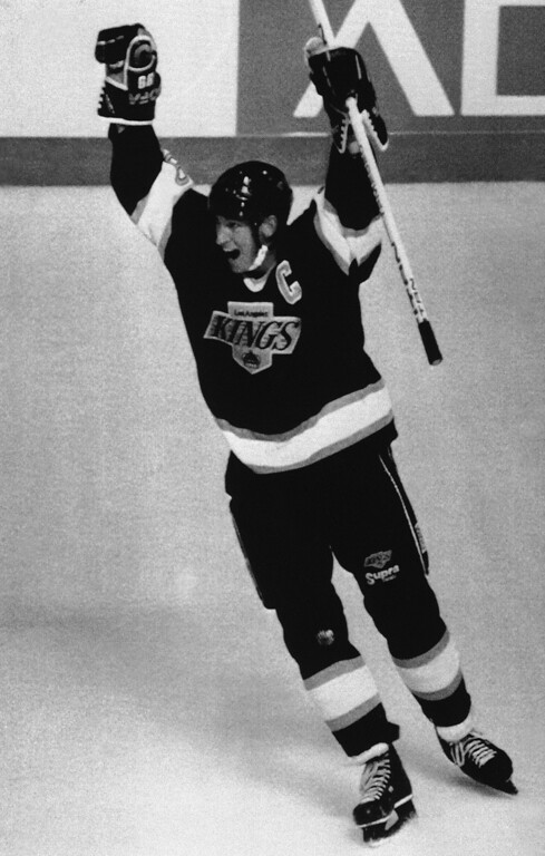 . Los Angeles Kings Wayne Gretzky raises his arms in jubilation after assisting in the Kings final goal to win 6-5 over the Vancouver Canucks in Vancouver at night on Friday, Oct. 14, 1989.   It was Gretzky\'s third assist of the night putting him within two points of the NHL all-time scoring record set by Gordie Howe. (AP Photo/Jon Murray)