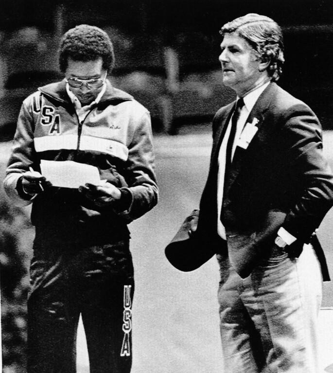 . U.S. Davis Cup team captain Arthur Ashe reads the referee\'s report, Dec. 17, 1984, as referee Alan Mills of England looks on.  (AP Photo/Goran Strandberg)