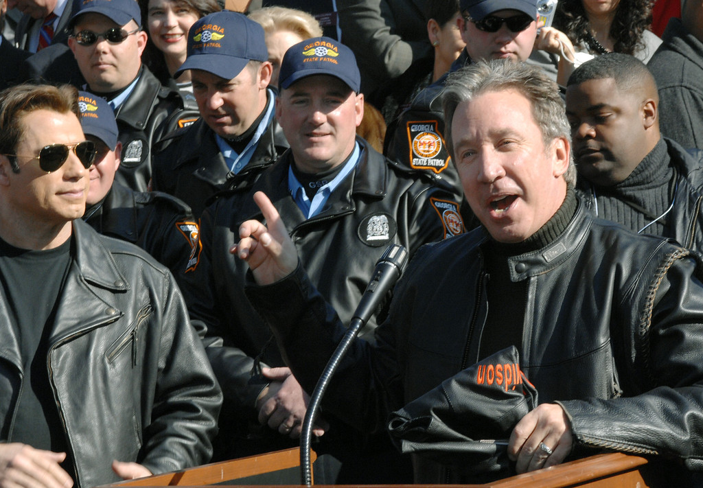 ". Actors Tim Allen, right, speaks as actor John Travolta, left, looks on, during a news conference for the ""Wild Hogs Motorcycle Safety Awareness Day\"" Tuesday, Feb. 6, 2007 at the Capitol in Atlanta. (AP Photo/Gregory Smith)"