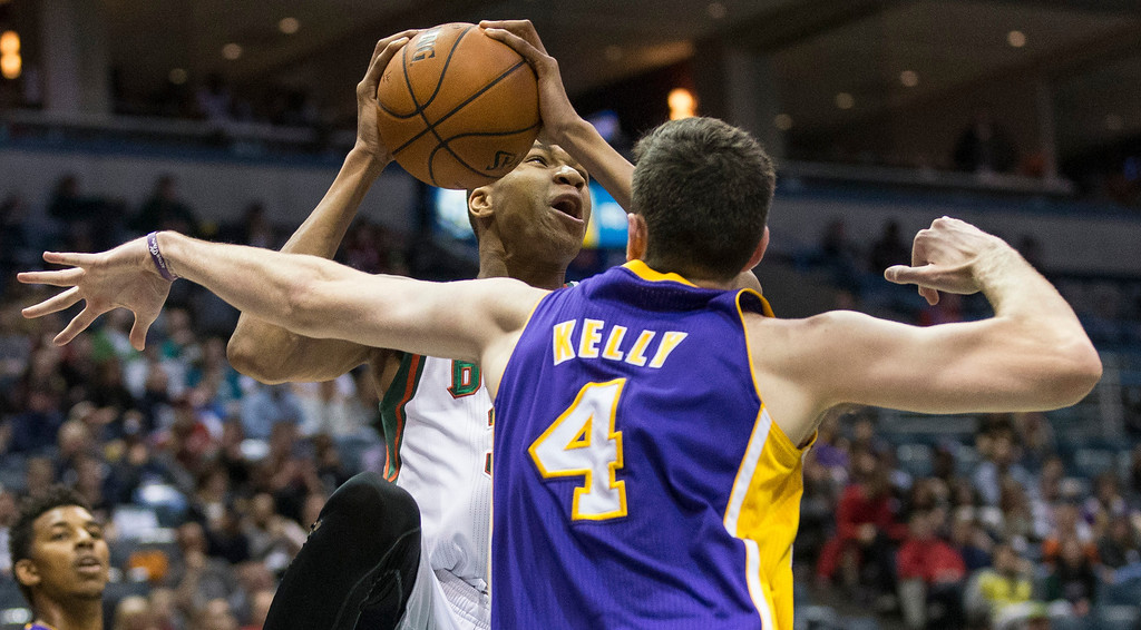 . Milwaukee Bucks\' Giannis Antetokounmpo looks to pass the ball against the Los Angeles Lakers\' Ryan Kelly during the second half of an NBA basketball game Thursday, March 27, 2014, in Milwaukee. (AP Photo/Tom Lynn)