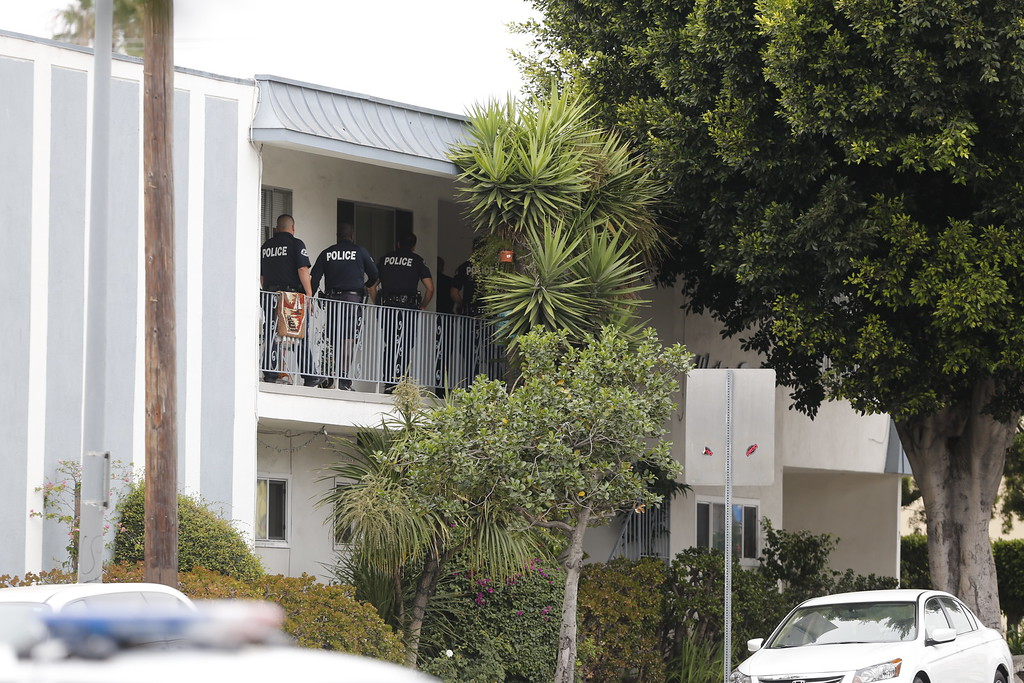 . Los Angeles police officers check a home in the city\'s westside Palms district, that was believed to be connected in some way with shootings in nearby Santa Monica,. Calif., Friday, June 7, 2013. A gunman with an assault-style rifle killed at least six people in Santa Monica on Friday before police shot him to death in a gunfight in a college library, authorities said.  Police Chief Jacqueline Seabrooks told reporters the rampage began at a house in the coastal city before the gunman, dressed all in black, made his way to Santa Monica College.  (AP Photo/Reed Saxon)