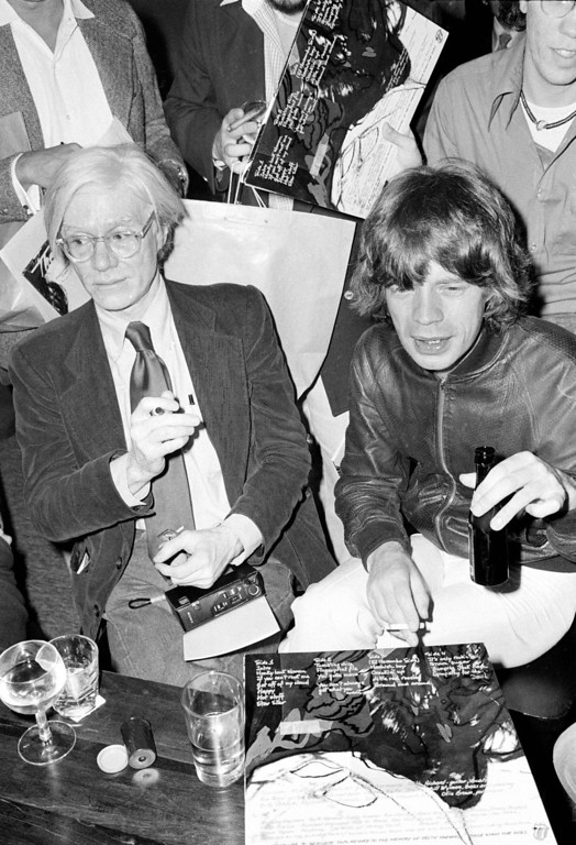 ". Rolling Stones lead singer Mick Jagger, right, is shown with pop artist Andy Warhol during a promotion for his band\'s new album, ""Love You Live,\"" at Trax, a midtown New York City nightspot, Friday, Sept. 23, 1977.   (AP Photo)"