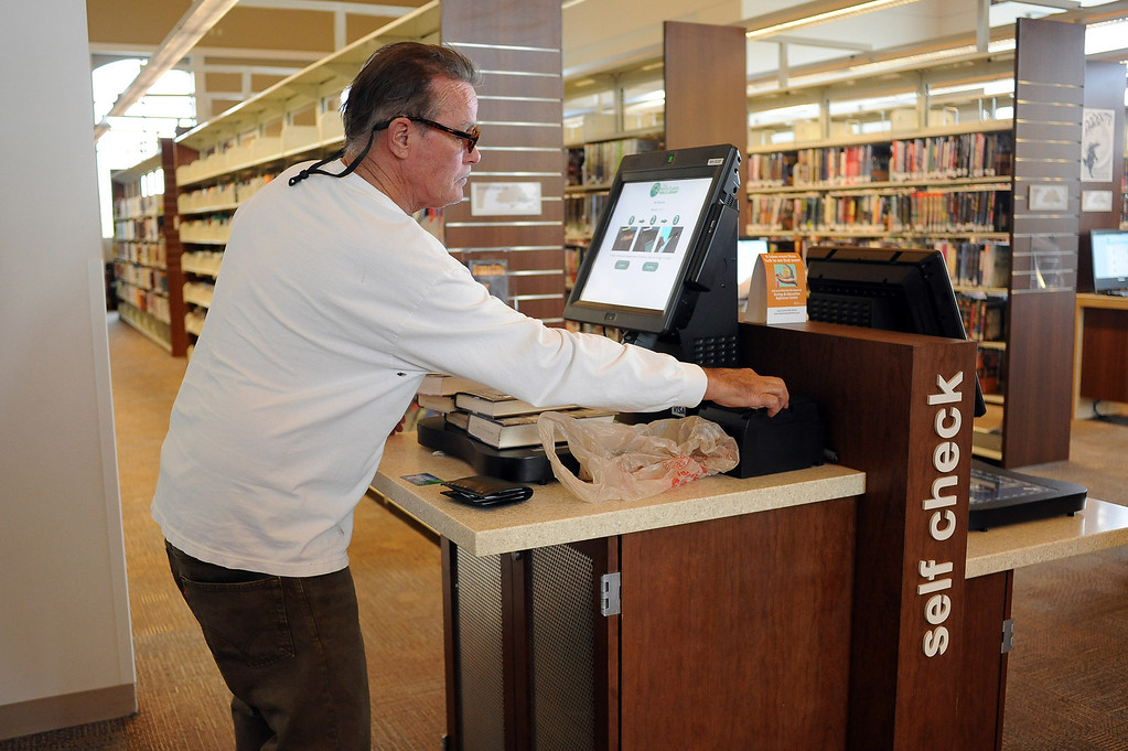 . Brian Thomson takes advantage of a self checkout station at the Old Town Newhall Library November 12, 2103.  Libraries have evolved into more comfortable places that cater to digital reading habits, with computers and more public meeting spaces.(Andy Holzman/Los Angeles Daily News)