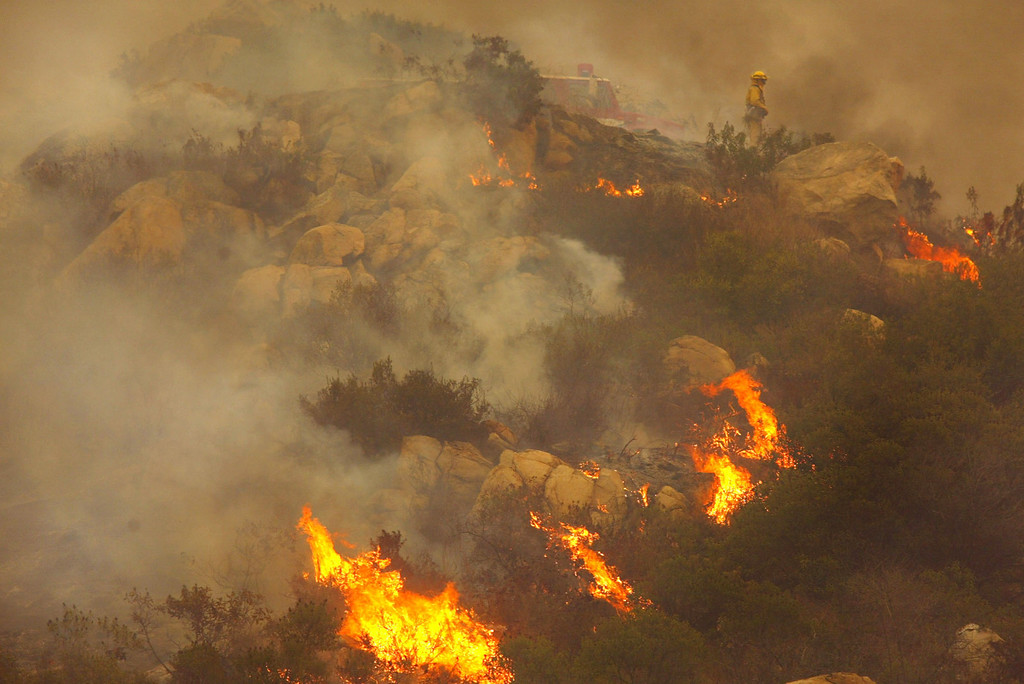. SAN DIEGO - OCTOBER 27:  Dry trees and brush burn as firecrews attempt to control the Cedar Fire October 27, 2003 near Lakeside in San Diego, California. The death toll stands at 13, with more than 1,000 homes being reduced to ashes as southern California fires continue to burn. Winds have eased a bit, but 30,000 homes remain threatened by the fires, which have charred more than 400,000 acres, according to officials. Davis, who has activated the National Guard, predicted damages will be in the billions of dollars.  (Photo by Donald Miralle/Getty Images)