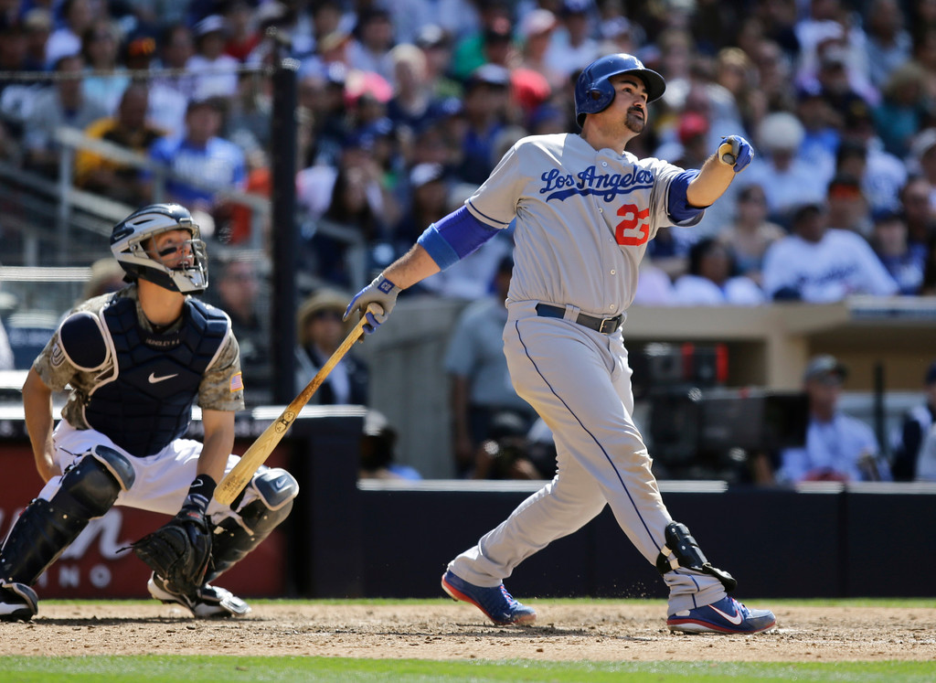 . Los Angeles Dodgers\' Adrian Gonzalez and San Diego Padres catcher Nick Hundley, left, watch the flight of Gonzalez\' ninth-inning home run gaving the Dodgers the lead in a baseball game eventually won by the Dodgers 3-1 in San Diego, Sunday, June 23, 2013. (AP Photo/Lenny Ignelzi)