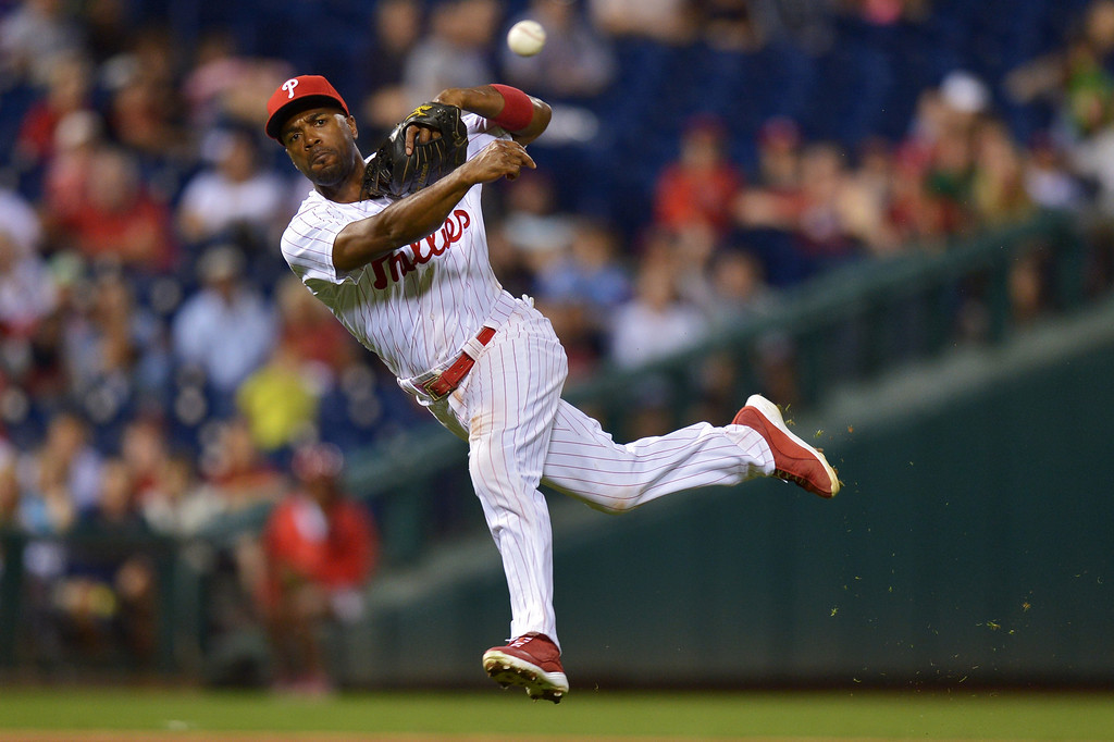 . PHILADELPHIA, PA - AUGUST 16: Jimmy Rollins #11 of the Philadelphia Phillies makes a jumping throw to first base trying to put out Hanley Ramirez #13 of the Los Angeles Dodgers on an infield single at Citizens Bank Park on August 16, 2013 in Philadelphia, Pennsylvania. The Dodgers won 4-0. (Photo by Drew Hallowell/Getty Images)