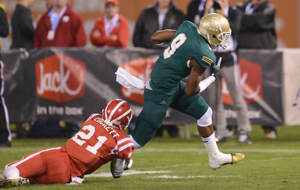 . Anaheim, Calif., --12-01-12 - Long Beach Poly\'s John Smith,9, breaks free from Mater Dei\'s Jonathan Lockett,21, for a touchdown in the 1st quarter  of the CIF-SS Pac-5 Division final game at Anaheim Stadium.   Stephen Carr/  LANG
