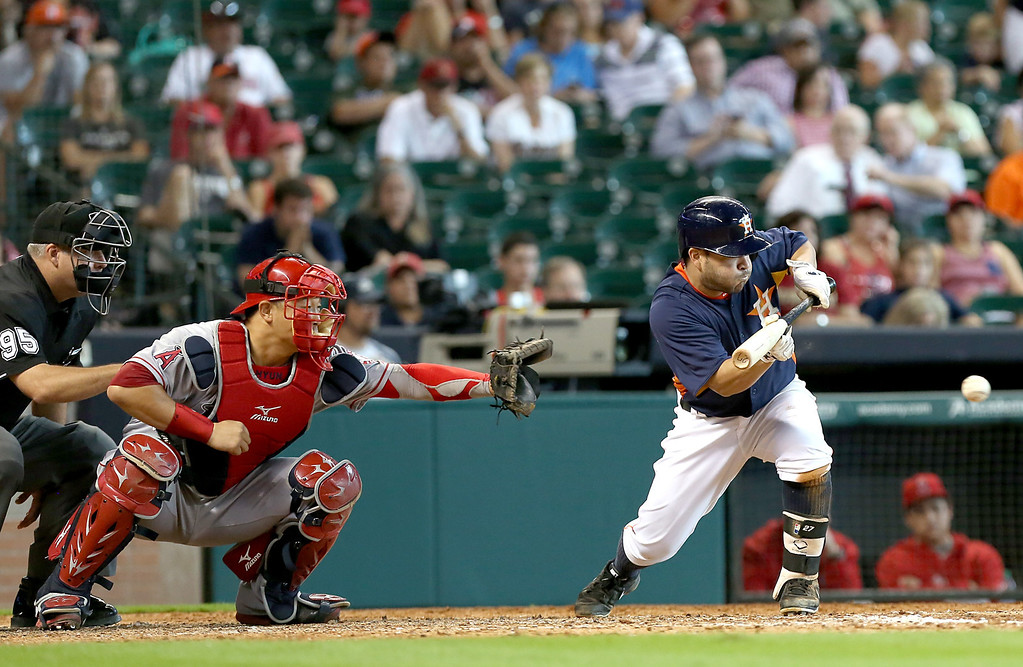 . HOUSTON, TX - SEPTEMBER 15: Jose Altuve #27 of the Houston Astros lays down a sacrifice bunt agains the Los Angeles Angels of Anaheim in the eighth inning on September 15, 2013 at Minute Maid Park in Houston, Texas. (Photo by Thomas B. Shea/Getty Images)