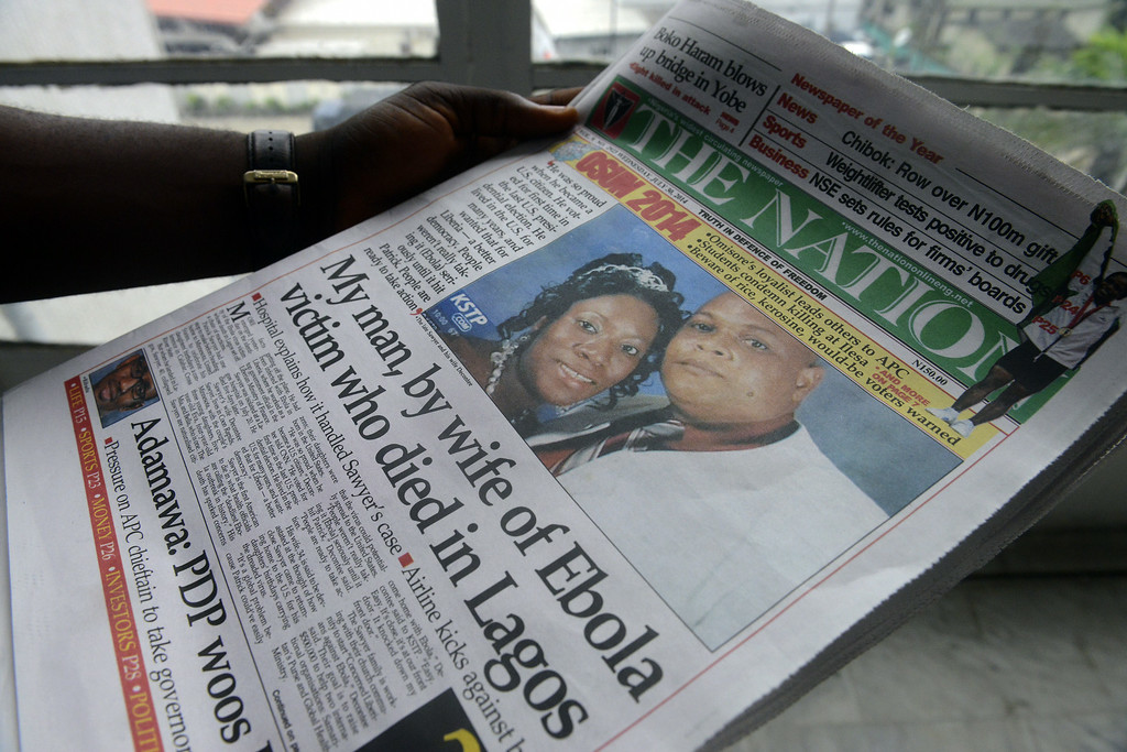 . A man reads a newspaper featuring a front page story on the death of Liberian diplomat Patrick Sawyer (pictured with his wife Decontee) who died of the Ebloa virus in Lagos on July 30, 2014. Nigeria is on alert against the possible spread of Ebola after the first confirmed death from the virus in Lagos, Africa\'s biggest city and the country\'s financial capital. The victim, who worked for the Liberian government, collapsed at Lagos international airport after arriving on a flight from Monrovia via the Togolese capital Lome, according to the Nigerian government. Doctors Without Borders (MSF) warned that the crisis gripping Guinea, Liberia and Sierra Leone would only get worse and could not rule out it spreading to other countries.         (PIUS UTOMI EKPEI/AFP/Getty Images)