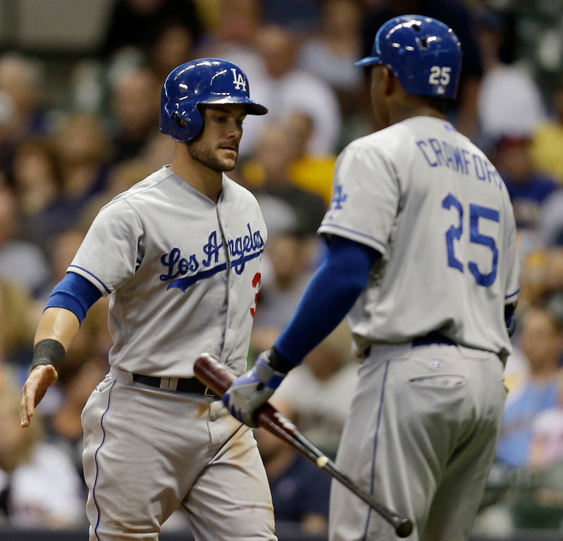 . MILWAUKEE, WI - MAY 21: Skip Schumaker #3 of the Los Angeles Dodgers celebrates with Carl Crawford #25 after reaching on a single hit by Zack Greinke in the top of the fourth inning against the Milwaukee Brewers at Miller Park on May 21, 2013 in Milwaukee, Wisconsin. (Photo by Mike McGinnis/Getty Images)